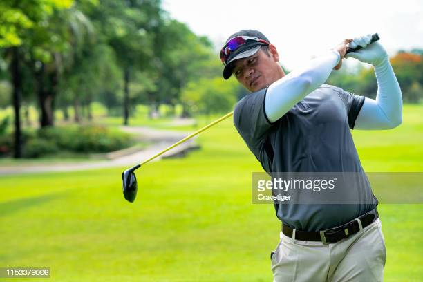 golfer hitting golf shot with club on course while on summer vacation. golfer swings his driver off the tee. - play off stock pictures, royalty-free photos & images