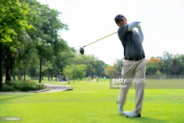golfer hitting golf shot with club on course while on summer vacation. golfer swings his driver off the tee. - golfer stock pictures, royalty-free photos & images