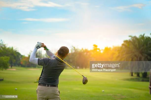 golfer hitting golf shot with club on course while on summer vacation - ゴルフ ストックフォトと画像