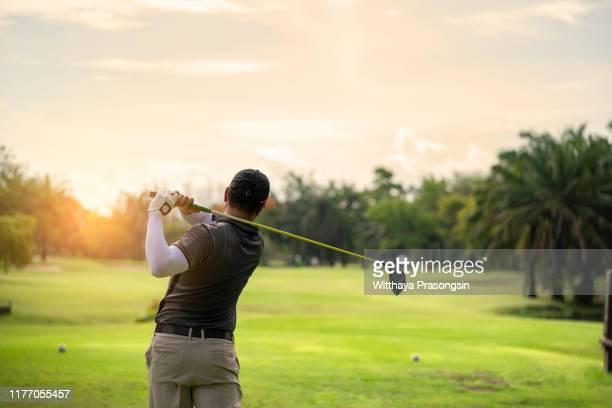 golfer hitting golf shot with club on course while on summer vacation - golfschwung stock-fotos und bilder