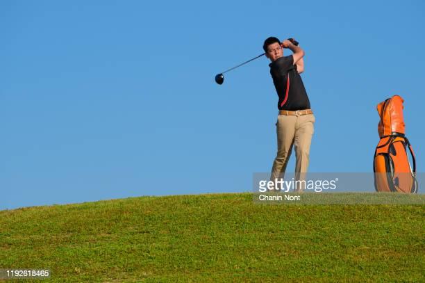 golfer hitting golf shot with club on course while on summer vacation - ゴルフクラブ ドライバー ストックフォトと画像