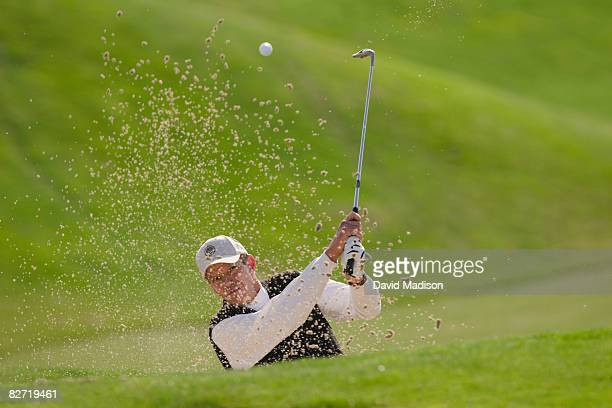 Golfer hitting out of bunker or sand trap.