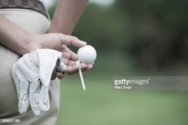 golfer holding a golf ball and a tee and a golf glove. - golftee stock-fotos und bilder