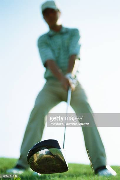 golfer holding golf club, focus on club in foreground, low angle view - driver golf club stock pictures, royalty-free photos & images