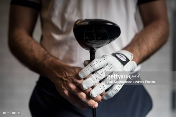 golfer holding golf club - golf club stock pictures, royalty-free photos & images