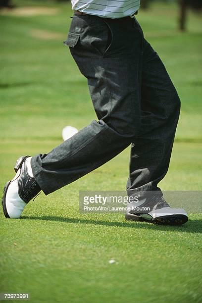 Golfer in mid swing, low section