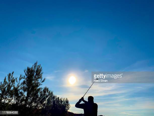 golfer in silhouette with golf swing against sun - france strike stock pictures, royalty-free photos & images