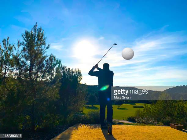 golfer in silhouette with golf swing and ball against sun - france strike stock pictures, royalty-free photos & images