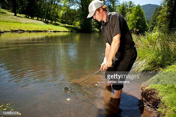 golfer in the water hazard. - wading stock pictures, royalty-free photos & images