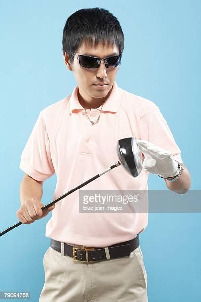 A golfer inspecting his golf club.