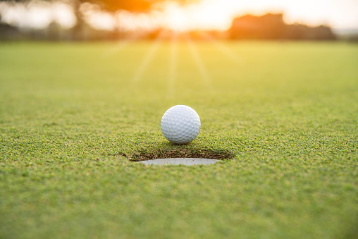 Golfer is putting golf ball on green grass at golf course for game with blur background and sunlight ray 1127900797
