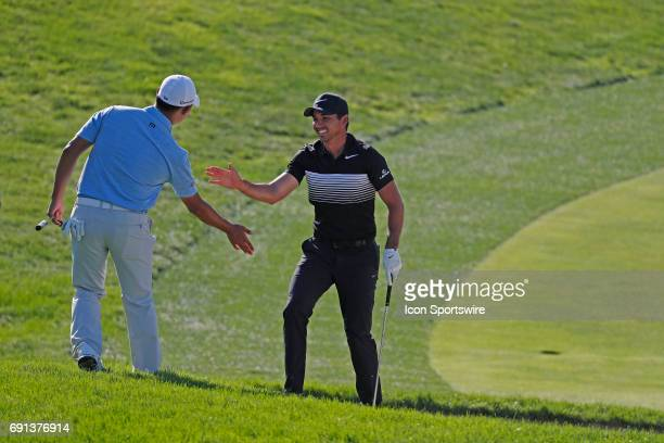 Golfer Jason Day gets a high five from Si Woo Kim after holing out of a sand trap for a birdie on the 18th hole during the first round of the...