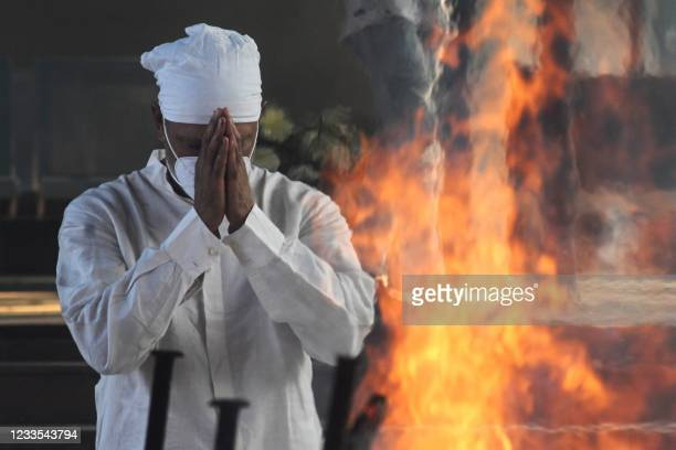 Golfer Jeev Milkha offer prayers in front of the funeral pyre of his dad and track legend Milkha Singh, who died aged 91 following a long battle with...