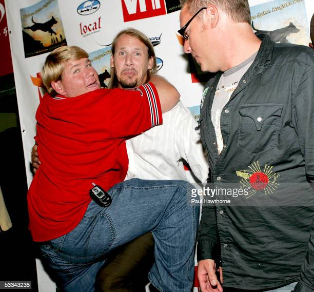 Golfer John Daly jokes with Hootie and the Blowfish band members Jim Soni Sonefeld and Dean Felber as they attend a listening party for their new CD...