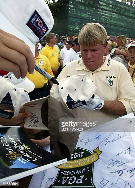 US golfer John Daly signs an autograph during his practice round for the 2002 PGA Championship13 August 2002 at Hazeltine National Golf Club in...