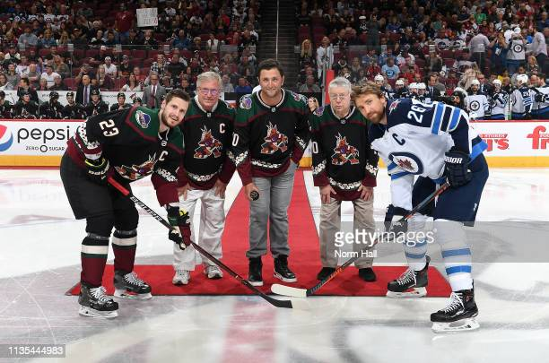 Golfer Jon Rahm , along with Gregory Cooper and Joel Weisheit, prepares to drop the ceremonial puck between Oliver Ekman-Larsson of the Arizona...