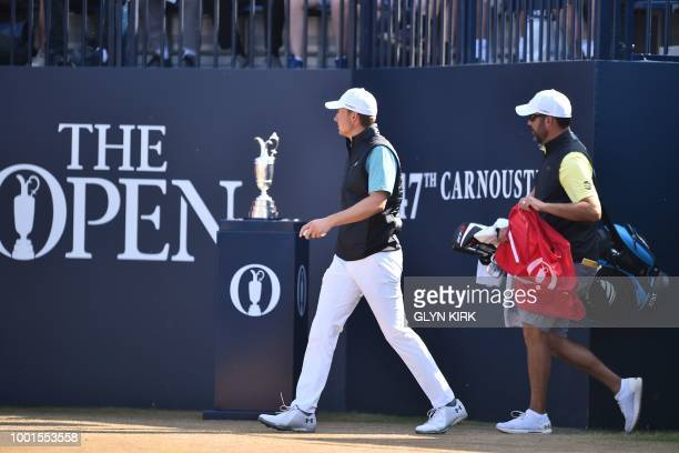 US golfer Jordan Spieth and his caddie Michael Greller walk past the claret jug on the 1st tee ahead of his first round on day one of The 147th Open...