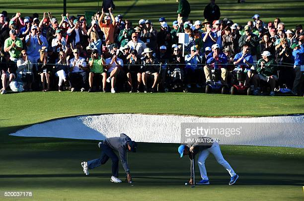 US golfer Jordan Spieth and Northern Ireland's Rory McIlroy mark their balls during Round 3 of the 80th Masters Golf Tournament at the Augusta...