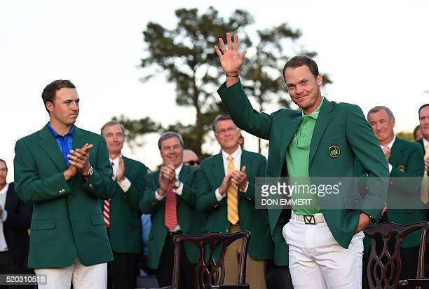 US golfer Jordan Spieth applauds as England's Danny Willett waves wearing his Green Jacket at the end of the 80th Masters Golf Tournament at the...
