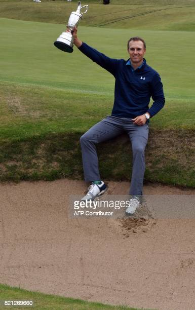 US golfer Jordan Spieth in a bunker on the 18th hole poses for pictures with the Claret Jug the trophy for the Champion golfer of the year after...