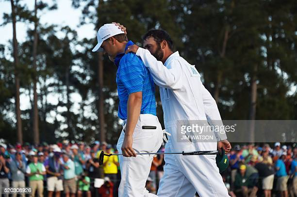 US golfer Jordan Spieth is comforted by his caddie Michael Greller as they leave the 18th green during Round 4 of the 80th Masters Golf Tournament at...