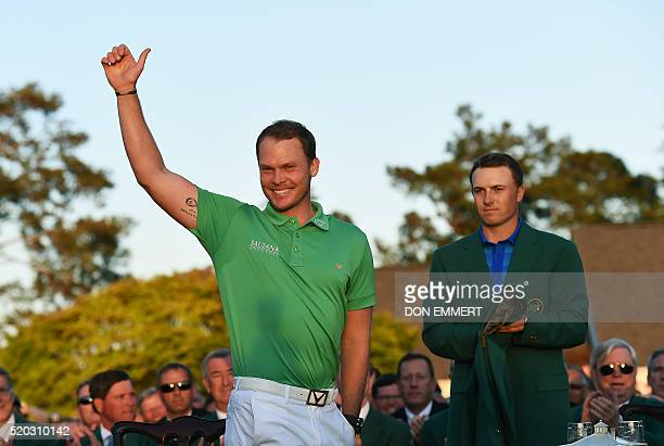 US golfer Jordan Spieth looks on as England's Danny Willett waves during presentation ceremony at the end of the 80th Masters Golf Tournament at the...