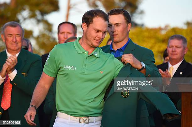 US golfer Jordan Spieth presents the Green Jacket to England's Danny Willett at the end of the 80th Masters Golf Tournament at the Augusta National...
