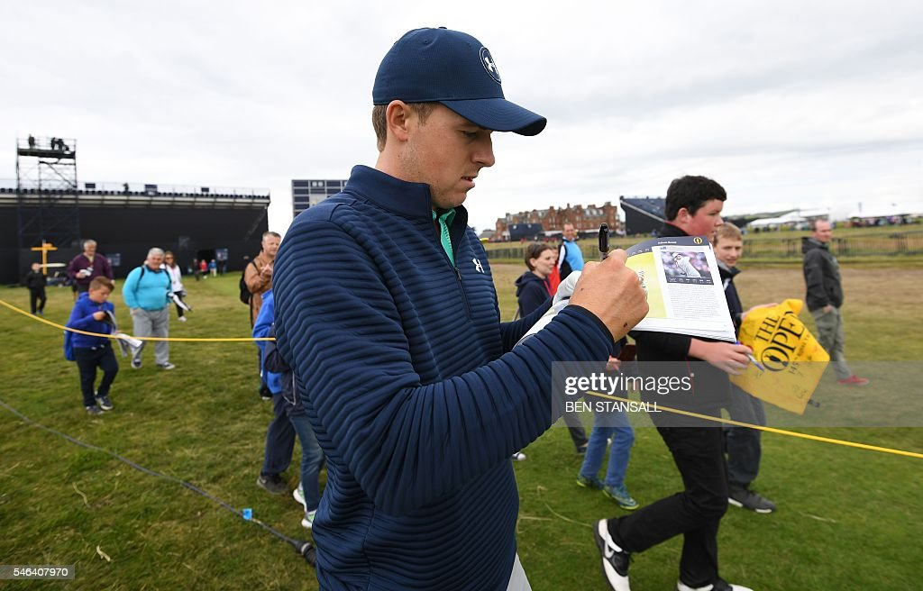 US golfer Jordan Spieth signs autographs while walking up the 2nd faitway during practice on July 12, 2016, ahead of the 2016 British Open Golf Championship at Royal Troon in Scotland. The 2016 British Open begins on July 14, 2016. The British Open returns to Royal Troon on Scotland's west coast this week with Rory McIlroy back in the field having been unable to defend the Claret Jug a year ago due to injury. / AFP / Ben STANSALL / RESTRICTED