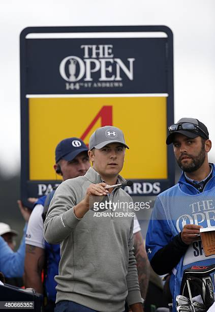 US golfer Jordan Spieth talks with his caddie Michael Greller as they wait on the 4th tee during a practice round on The Old Course at St Andrews in...