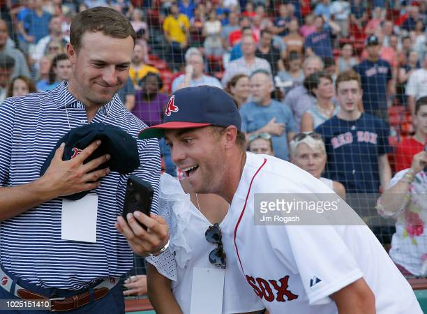 Golfer Justan Thomas looks at a photo taken by golfer Jordan Spieth of Thomas earlier throwing out the first pitch at Fenway Park before a game...