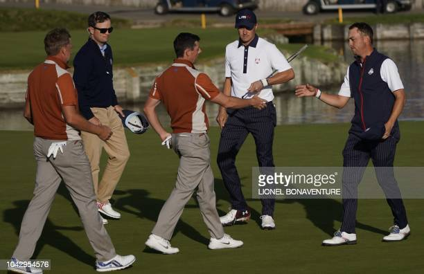 US golfer Justin Thomas and US golfer Jordan Spieth shake hands with Europe's Northern Irish golfer Rory McIlroy and Europe's English golfer Ian...