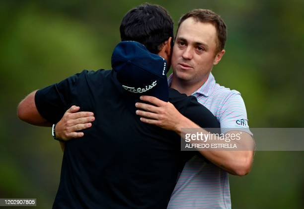 US golfer Justin Thomas congratulates US golfer Patrick Reed on the 18th green during the fourth and last round of the World Golf Championship at...