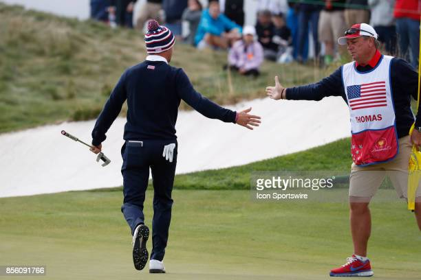 USA golfer Justin Thomas gets a high five from his caddie after making a long birdie putt on the 14th hole during the third round of the Presidents...
