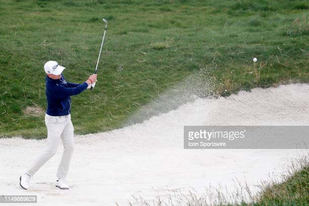 Golfer Justin Thomas hits out of a sand trap on the 17th hole during a practice round for the 2019 US Open on June 12 at Pebble Beach Golf Links in...
