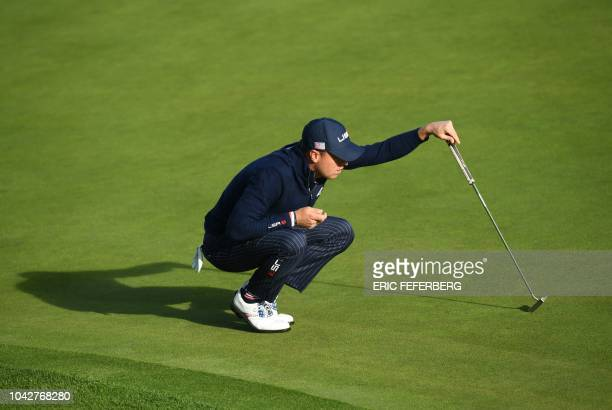 US golfer Justin Thomas lines up a putt during his fourball match on the second day of the 42nd Ryder Cup at Le Golf National Course at...