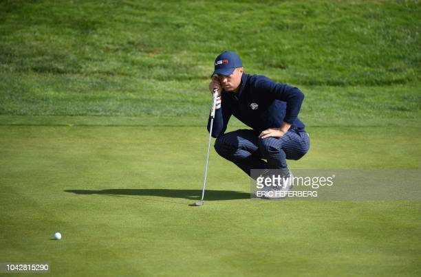 TOPSHOT US golfer Justin Thomas lines up a putt during his fourball match on the second day of the 42nd Ryder Cup at Le Golf National Course at...