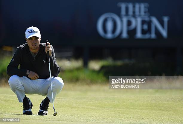 US golfer Justin Thomas lines up a putt on the 14th Green during his first round 67 on the opening day of the 2016 British Open Golf Championship at...