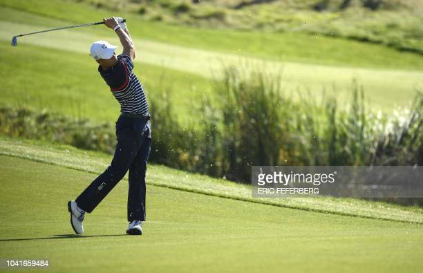 TOPSHOT US golfer Justin Thomas plays a fairway shot during a practice session ahead of the 42nd Ryder Cup at Le Golf National Course at...