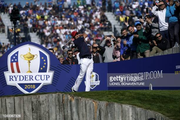 US golfer Justin Thomas plays a tee shot during his singles match with Europe's Northern Irish golfer Rory McIlroy on the third day of the 42nd Ryder...