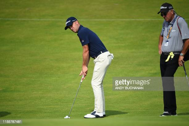 Golfer Justin Thomas plays puts on the 11th green at The 148th Open golf Championship at Royal Portrush golf club in Northern Ireland on July 15,...