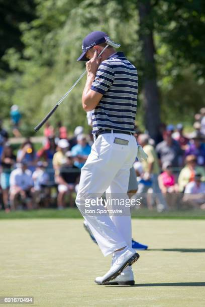 PGA golfer Justin Thomas puts his fingers in his ears as the crowd applauds for his long putt that went in the cup during the Memorial Tournament...