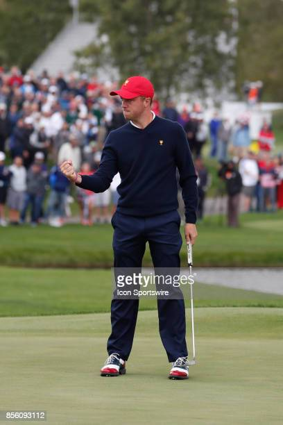 USA golfer Justin Thomas reacts to making a putt to halve the match on the 18th hole during the third round of the Presidents Cup at Liberty National...