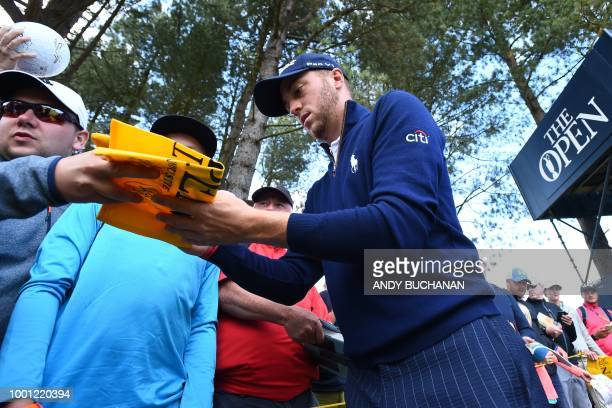 US golfer Justin Thomas signs autographs for fans during a practice round at The 147th Open golf Championship at Carnoustie Scotland on July 18 2018...