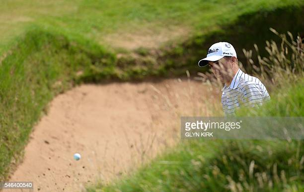 US golfer Justin Thomas watches his shot from a greenside bunker on the 8th hole during practice on July 12 ahead of the 2016 British Open Golf...