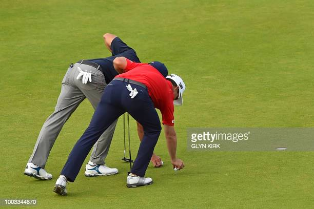 US golfer Kevin Kisner and US golfer Zach Johnson mark their balls on the 17th green during their third rounds on day 3 of The 147th Open golf...