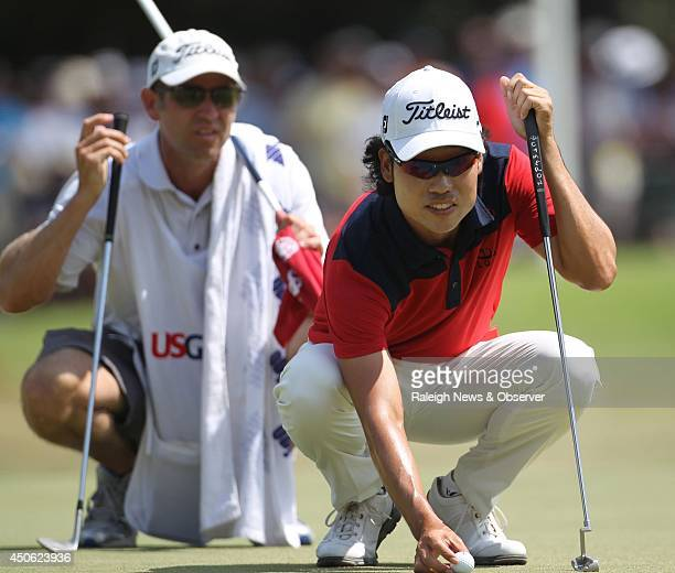 Golfer Kevin Na of Seoul South Korea lines up a putt on the first hole with his caddy Kenny Harms during the third round of the 2014 US Open at...