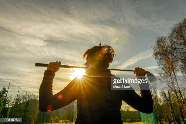golfer leaning her golf club on her shoulders and with sunbeam - golfer stock pictures, royalty-free photos & images