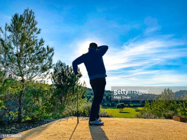 golfer leaning on golf club and watching the ball against sun - ティーショット ストックフォトと画像