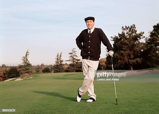 Golfer leaning on golf club