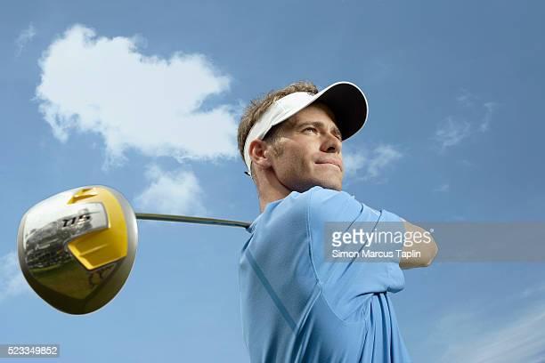 golfer looking at ball after swinging - ゴルフクラブ ドライバー ストックフォトと画像